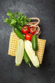 Vista superior de legumes frescos, tomates, pepinos, abóboras e verduras na superfície cinza
