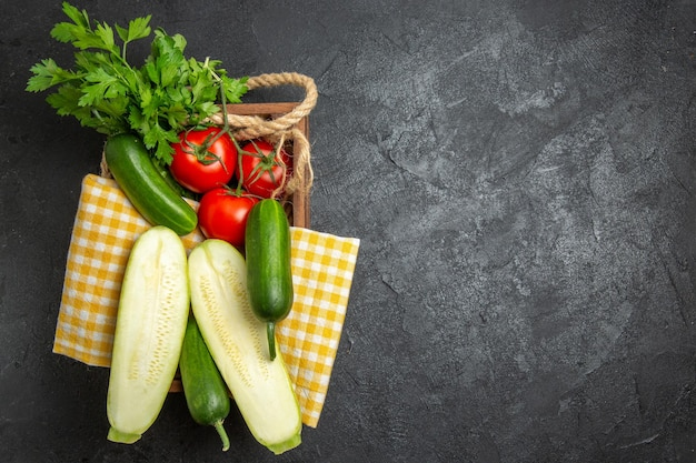 Vista superior de legumes frescos, tomates vermelhos, pepinos e abóboras com verduras na superfície cinza