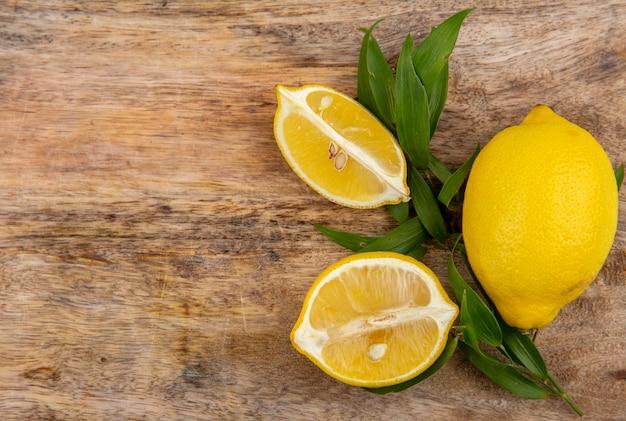 Vista superior de limão amarelo com estragão verde numa superfície de madeira