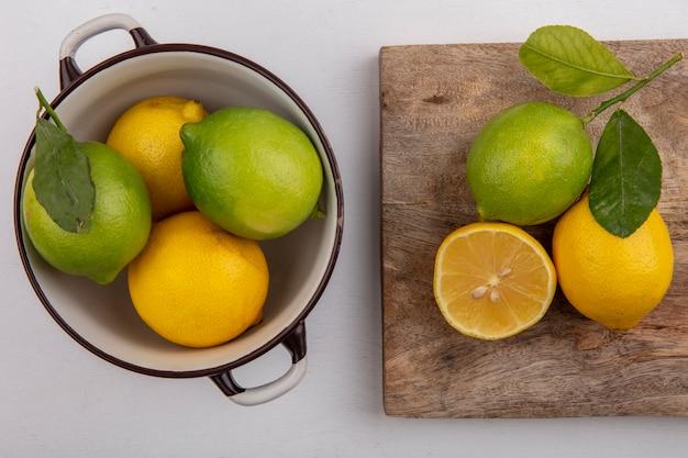 Vista superior de limão com limão em uma panela e em um quadro negro sobre fundo branco