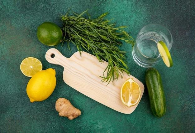 Vista superior de limão em uma placa de madeira da cozinha com gengibre com estragão verdes na superfície verde