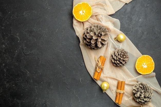 Vista superior de limas canela cortadas em laranjas e três cones de coníferas em uma toalha de cor nude sobre fundo de cor preta