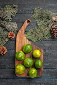 Vista superior de limas distantes a bordo de limas verdes na mesa da cozinha ao lado dos galhos e cones das árvores