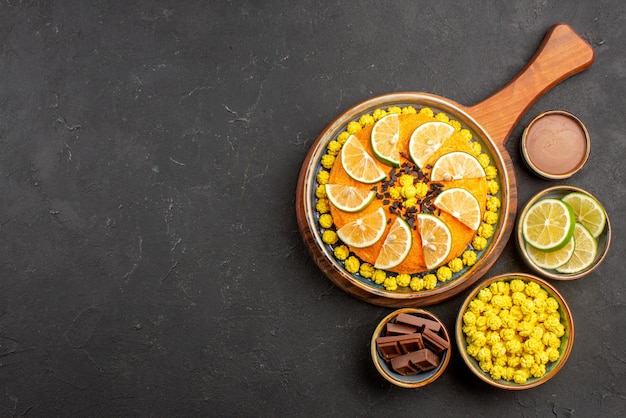 Vista superior de limas distantes e tigelas de doces de diferentes fatias de lima doces ao lado do bolo com frutas cítricas na tábua de corte na mesa preta