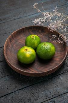 Vista superior de limas distantes em uma tigela três limas verdes em uma tigela de madeira ao lado dos galhos na mesa