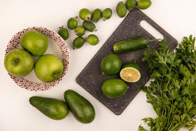 Vista superior de limas em uma mesa de cozinha com maçãs em uma tigela com feijoas de pepino e abacates isolados em uma parede branca