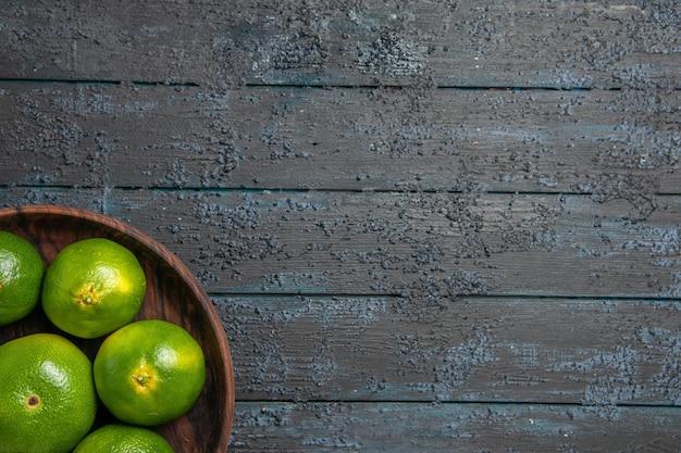 Vista superior de limas em uma tigela tigela de madeira marrom com muitas limas no lado esquerdo da mesa cinza