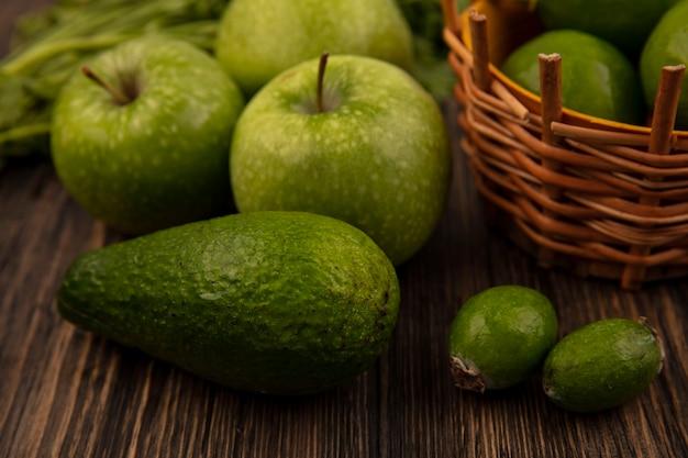 Vista superior de limas frescas em um balde com maçãs verdes feijoas abacate isoladas em uma parede de madeira