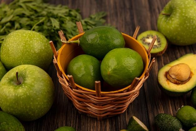 Vista superior de limas frescas em um balde com maçãs verdes kiwi feijoas abacates e salsa isolada em uma parede de madeira
