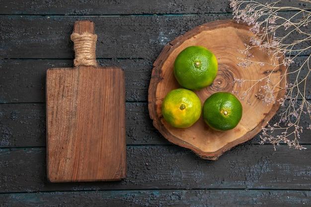 Vista superior de limas verdes ao longe em uma placa de madeira marrom ao lado da placa de corte e galhos na mesa cinza