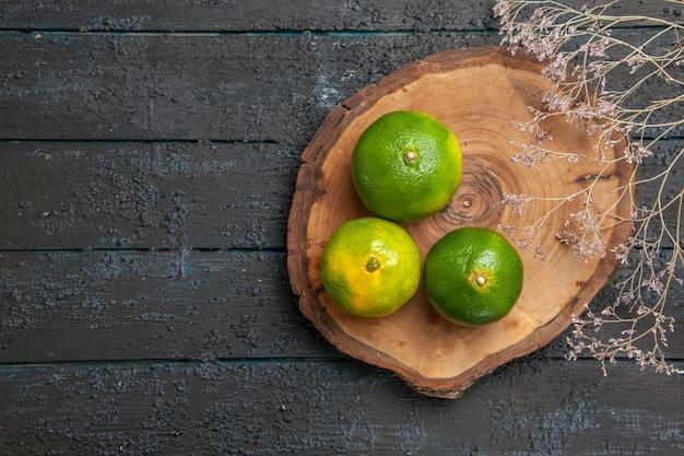 Vista superior de limas verdes ao longe em uma placa de madeira marrom no lado direito da mesa cinza ao lado dos galhos