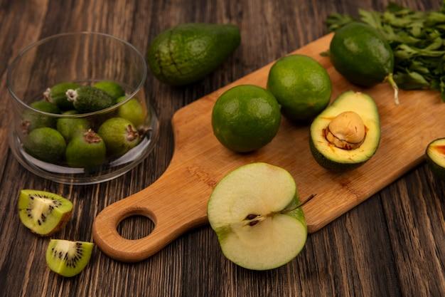Vista superior de limas verdes frescas em uma placa de cozinha de madeira com feijoas em uma tigela de vidro com abacate kiwi e salsa isolado em uma parede de madeira