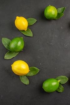 Vista superior de limões azedos frescos em frutas cítricas de lima cinza-escuro