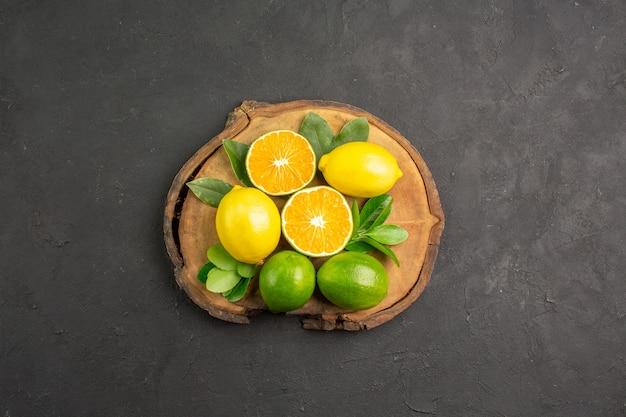Vista superior de limões azedos frescos em frutas cítricas limão de mesa escura