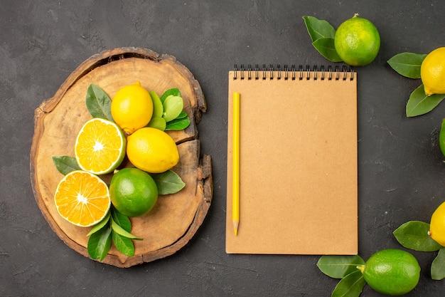 Vista superior de limões azedos frescos em frutas de mesa cinza-escuro e lima cítrica