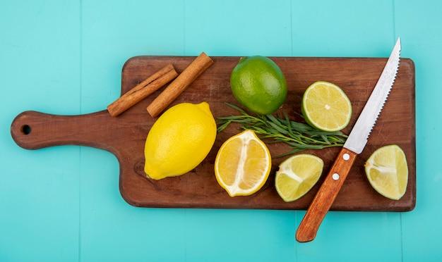 Vista superior de limões coloridos na mesa de madeira da cozinha com faca e paus de canela no azul