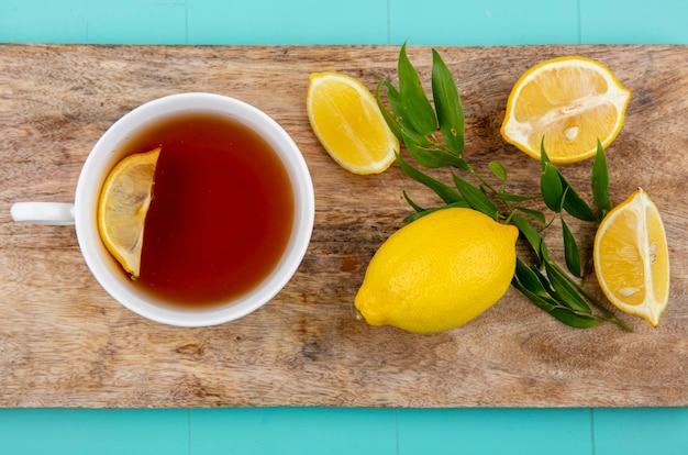 Vista superior de limões com estragão em uma placa de madeira da cozinha com uma xícara de chá na superfície azul