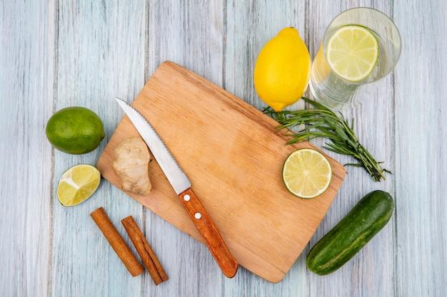 Vista superior de limões em uma placa de madeira da cozinha com faca com paus de gengibre e canela e estragão verdes na superfície de madeira cinza