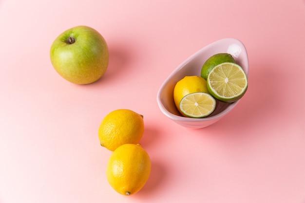 Vista superior de limões frescos com fatias de limão dentro do prato na superfície rosa claro