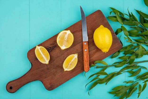 Vista superior de limões frescos e amarelos na mesa de cozinha de madeira com uma faca com folhas em azul