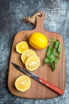 Vista superior de limões frescos e faca de hortelã em uma tábua de madeira