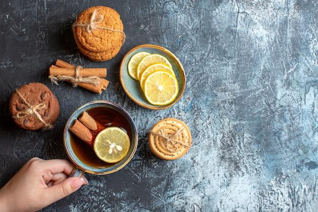 Vista superior de limões frescos e mão segurando uma xícara de chá preto com biscoitos de canela empilhados em fundo escuro