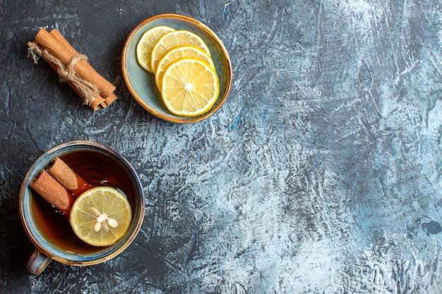 Vista superior de limões frescos e uma xícara de chá preto com canela no lado direito em fundo escuro