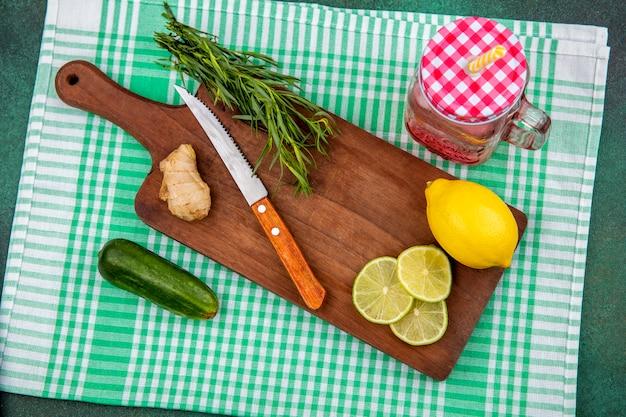 Vista superior de limões frescos em cozinha de madeira ampla com verduras de estragão e faca em toalha de mesa xadrez verde