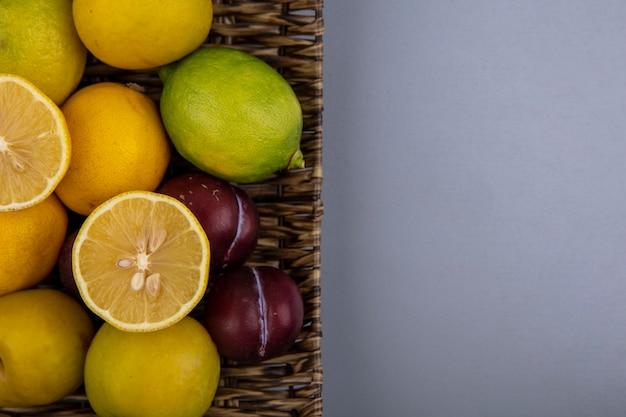 Vista superior de limões frescos em um balde com ameixas e ameixas cereja em um fundo cinza com espaço de cópia