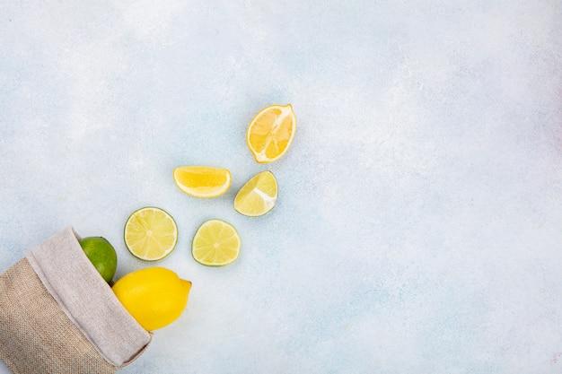 Vista superior de limões frescos em um saco de estopa com rodelas de limão isoladas em branco com espaço de cópia