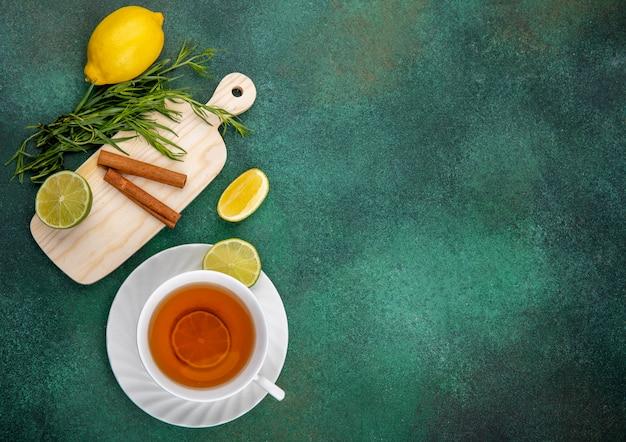 Vista superior de limões frescos na mesa de madeira da cozinha com verduras de estragão e paus de canela em verde com espaço de cópia