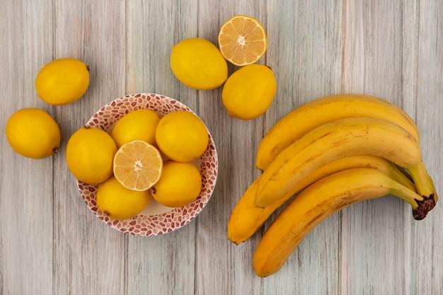 Vista superior de limões inteiros com sabor ácido em uma tigela com bananas isoladas em um fundo cinza de madeira