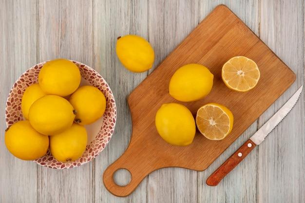 Vista superior de limões inteiros de forma arredondada em uma tigela com limões isolados em uma placa de cozinha de madeira com uma faca em uma parede de madeira cinza