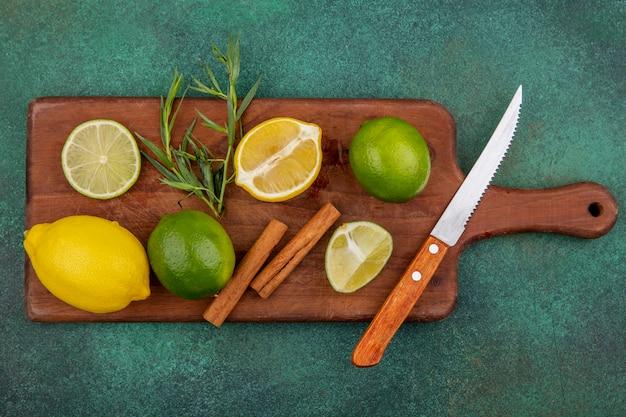 Vista superior de limões inteiros e fatiados coloridos na placa de cozinha de madeira com paus de canela com faca no verde