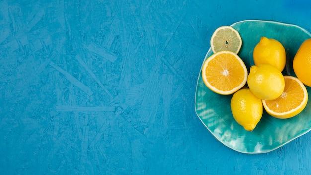 Vista superior de limões no prato com fundo azul