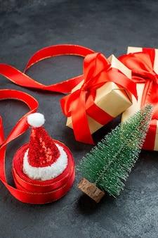 Vista superior de lindos presentes com fita vermelha e chapéu de papai noel com árvore de natal em uma mesa escura