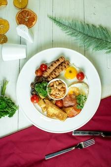 Vista superior de lingüiça frita e ovos com cogumelos tomate cereja e lobia em um prato branco