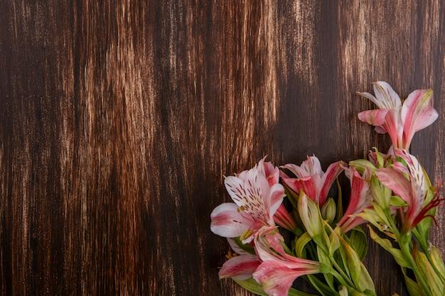 Vista superior de lírios cor de rosa na superfície de madeira