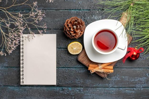 Vista superior de longe a árvore de natal galhos uma xícara de chá preto paus de canela na placa de madeira ao lado dos ramos de abeto de natal brinquedos da árvore caderno branco e limão