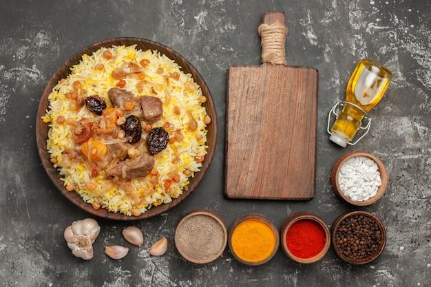 Vista superior de longe arroz pilaf com carne, especiarias coloridas, alho, óleo, tábua de cortar