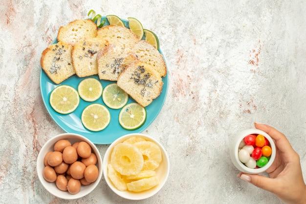 Vista superior de longe bolo de limão taças de doces na mão bolo com ervas de limão no prato