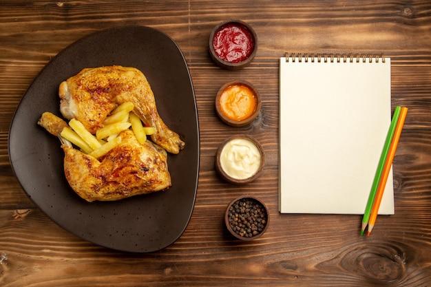 Vista superior de longe, caderno branco de fast food duas tigelas com molhos coloridos e pimenta preta ao lado do prato de frango e batatas fritas