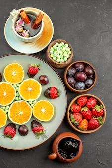 Vista superior de longe chocolate e frutas picadas laranja com cobertura de chocolate, doces verdes de morango e tigelas de calda de chocolate e frutas vermelhas na superfície escura