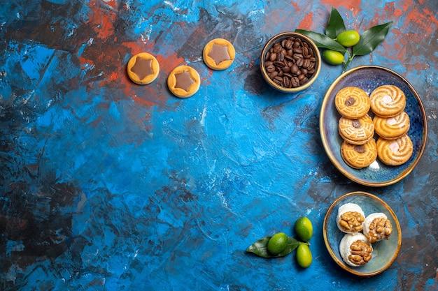 Vista superior de longe doces biscoitos diferentes, grãos de café, frutas cítricas