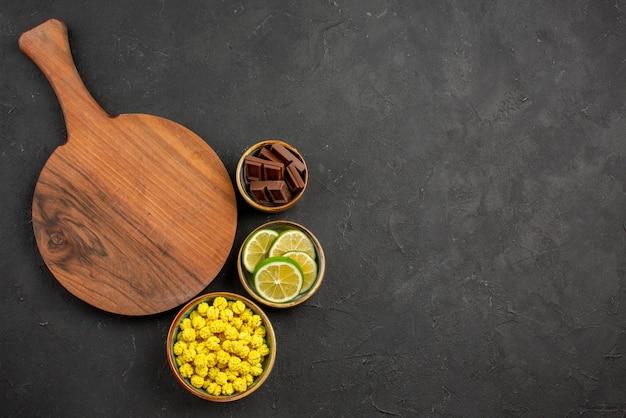 Vista superior de longe, doces, limas de chocolate e bombons amarelos em tigelas e a tábua de corte no fundo escuro