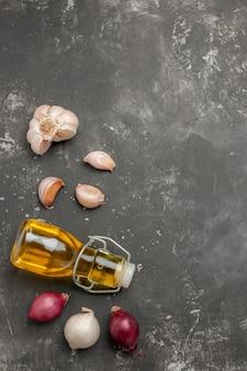 Vista superior de longe especiarias cebola alho garrafa de óleo na mesa escura