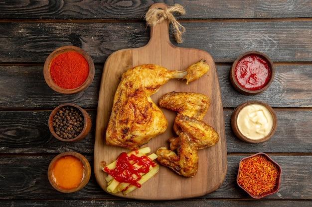Vista superior de longe frango batatas fritas asas de frango e perna e ketchup na tábua de madeira entre tigelas de molhos coloridos na mesa escura