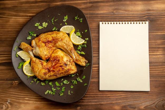 Vista superior de longe frango com caderno branco limão ao lado do prato de um apetitoso frango com ervas e limão na mesa de madeira