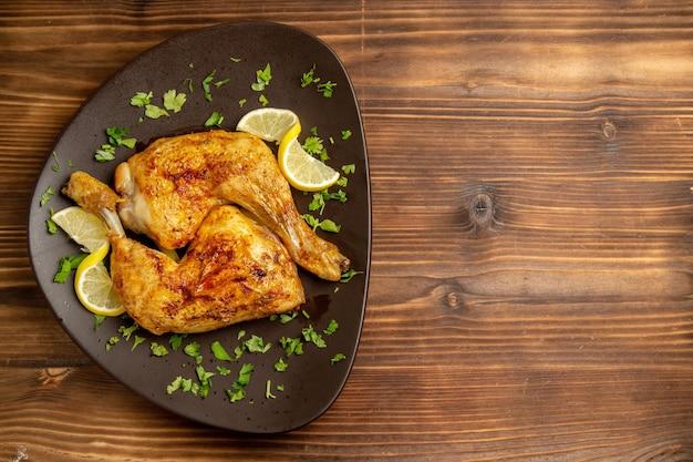 Vista superior de longe frango com coxinha de limão com ervas e limão no prato do lado esquerdo da mesa