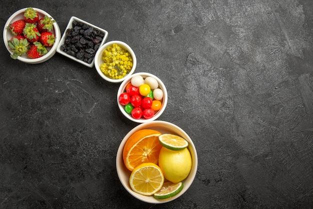 Vista superior de longe frutas cítricas diferentes doces frutas cítricas e morangos em tigelas no fundo escuro